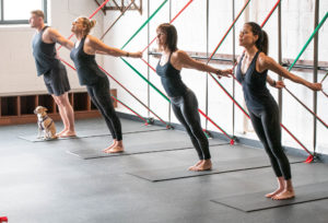 people stretching at BOARD30 studio in black workout attire after returning to the gym