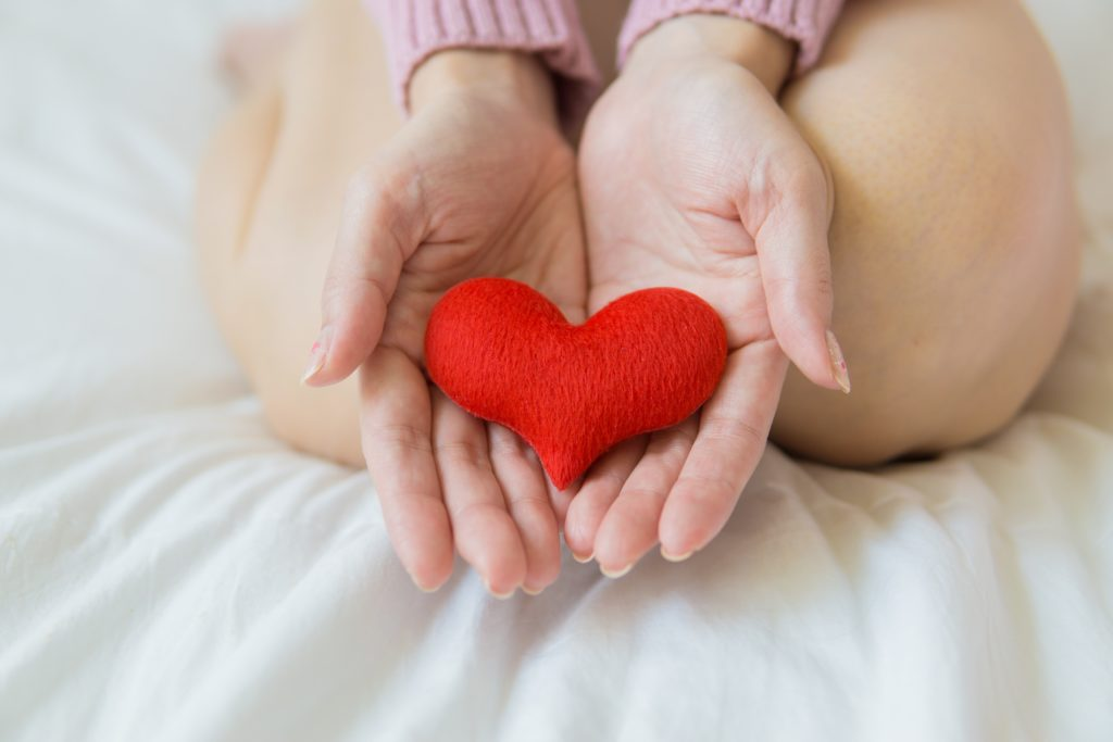person kneeling on white bed with red cloth heart in open hands to promote heart healthy snacking during heart month