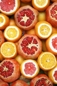 a mix of oranges and pomegranates sliced in half so their seeds show