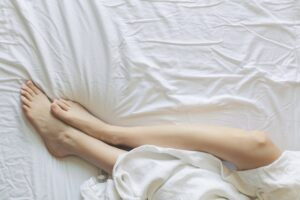 woman's feet laying in a bed with white sheets and bedding