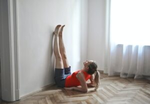 woman in workout clothes leaning up on elbows with her legs straight up against the wall