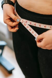 woman measuring waist with measuring tape