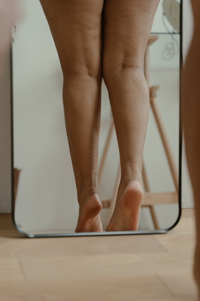 woman's legs standing in a mirror