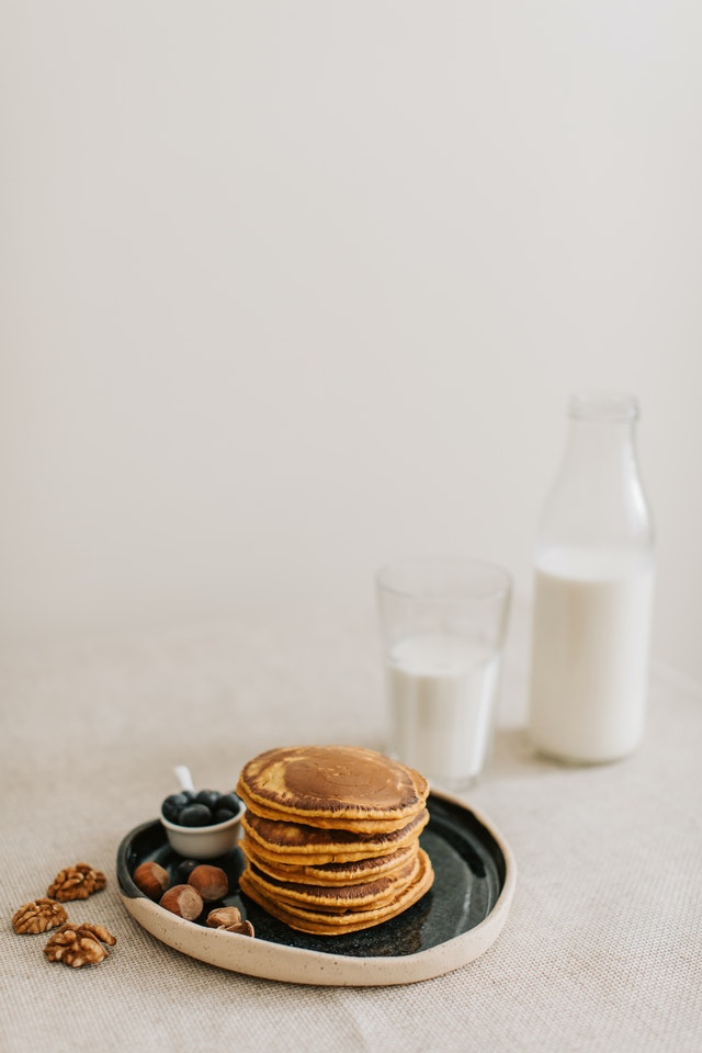 stack of pumpkin spice protein pancakes on a plate next to a glass of milk